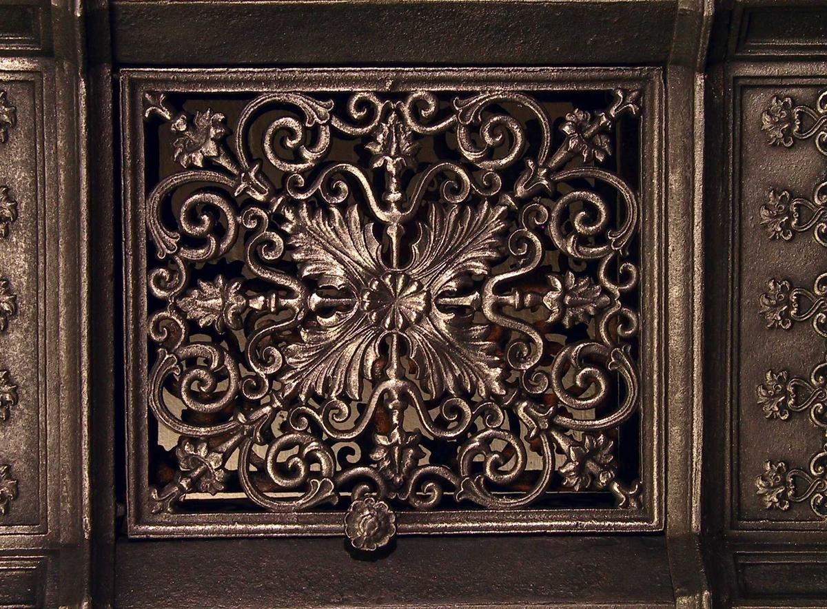 Firbladsrosett  3 tverrtromler m. symmetrisk horisontalt   kniplingsmønster,  6 sidetromler m. palmettmønster.