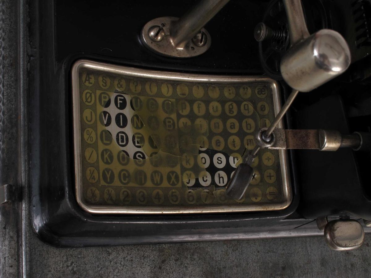 Bokstavtypene er støpt på en sylider som - når den rette bokstaven er i posisjon - slåes ned mot papiret. En pekestav stilles inn, det trykkes på en tast og bokstaven presses mot farvebåndet og papiret. Maskinen er sortlakkert og montert på en jernplate med en mykt underlag. Låsbart deksel hører til.