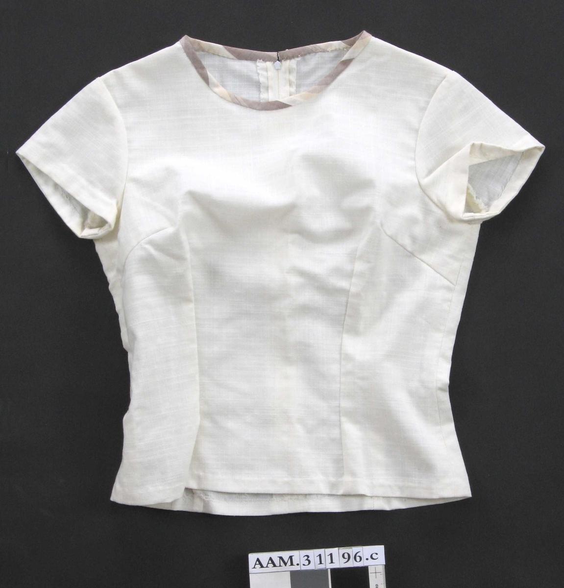 Figursydd, rund halsringning kantet med stoff som i jakke og skjørt, korte ermer, glidelås i ryggen.
