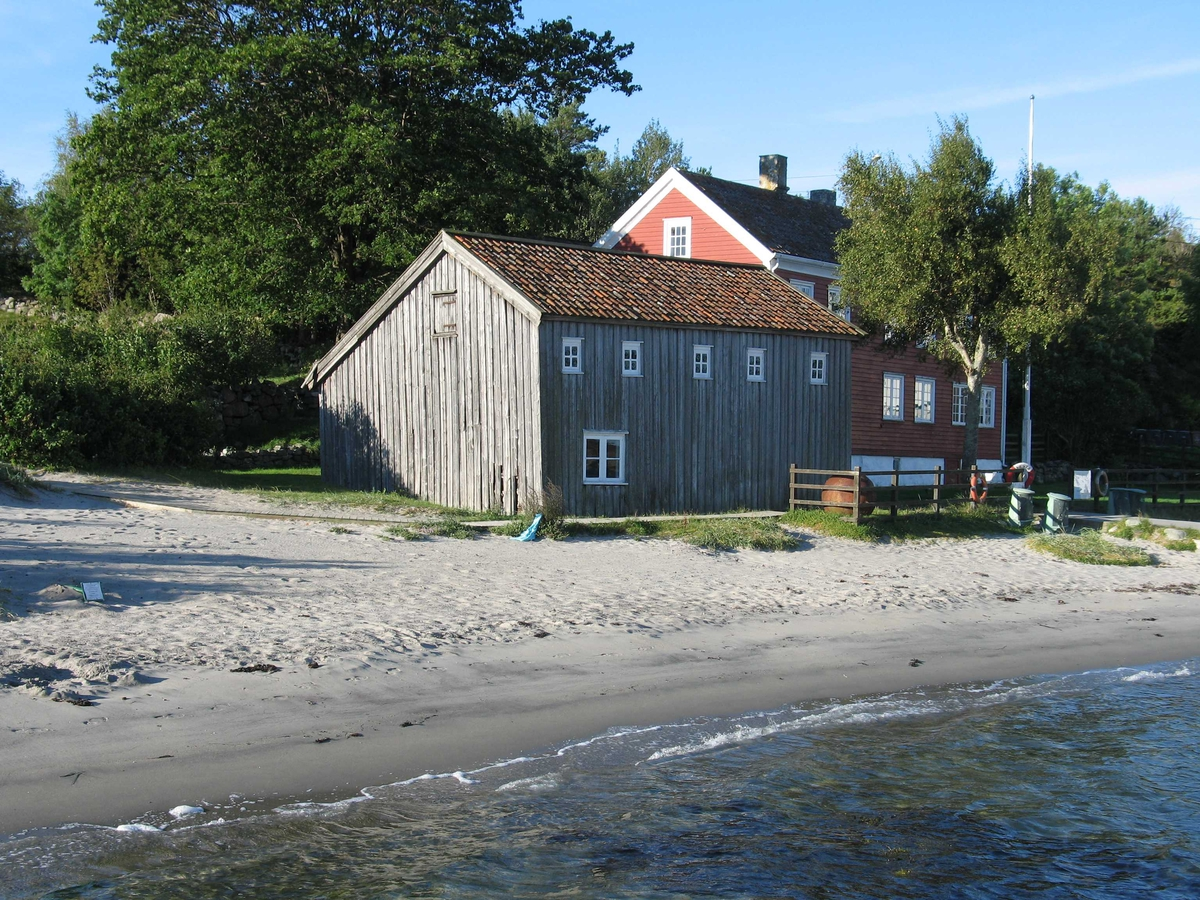 Merdøgaard sett fra øst. Stranda i forgrunnen, sjøboden sentralt. I bakgrunnen våningshuset.