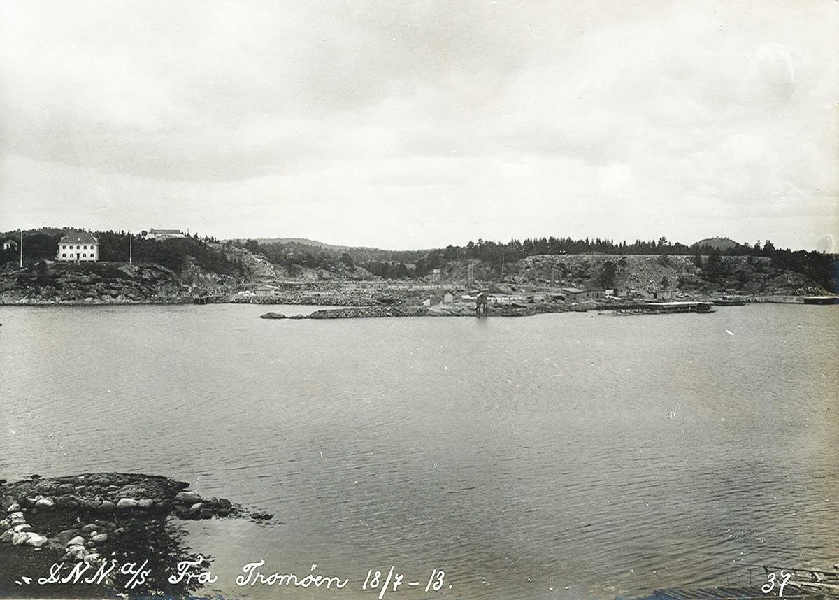 """""""18/07-1913"""" Nitridens fabrikkanlegg (tomter) sett fra Tromøya. Det hvite to-etasjes huset er direktørbolig for Smelteverket. Høydebassenget sees på toppen til høyre. Kai til høyre. Fabrikktomtens planering. Planeringen på høyden til høyre var tenkt til svovelsyrefabrikken, som ikke ble noe av. Midt på bildet sees en fyrlykt, satt opp på et skjær i 1894, men ble flyttet til Friisøy i 1929. Lykt nr. 612 i Norsk Fyrliste."""