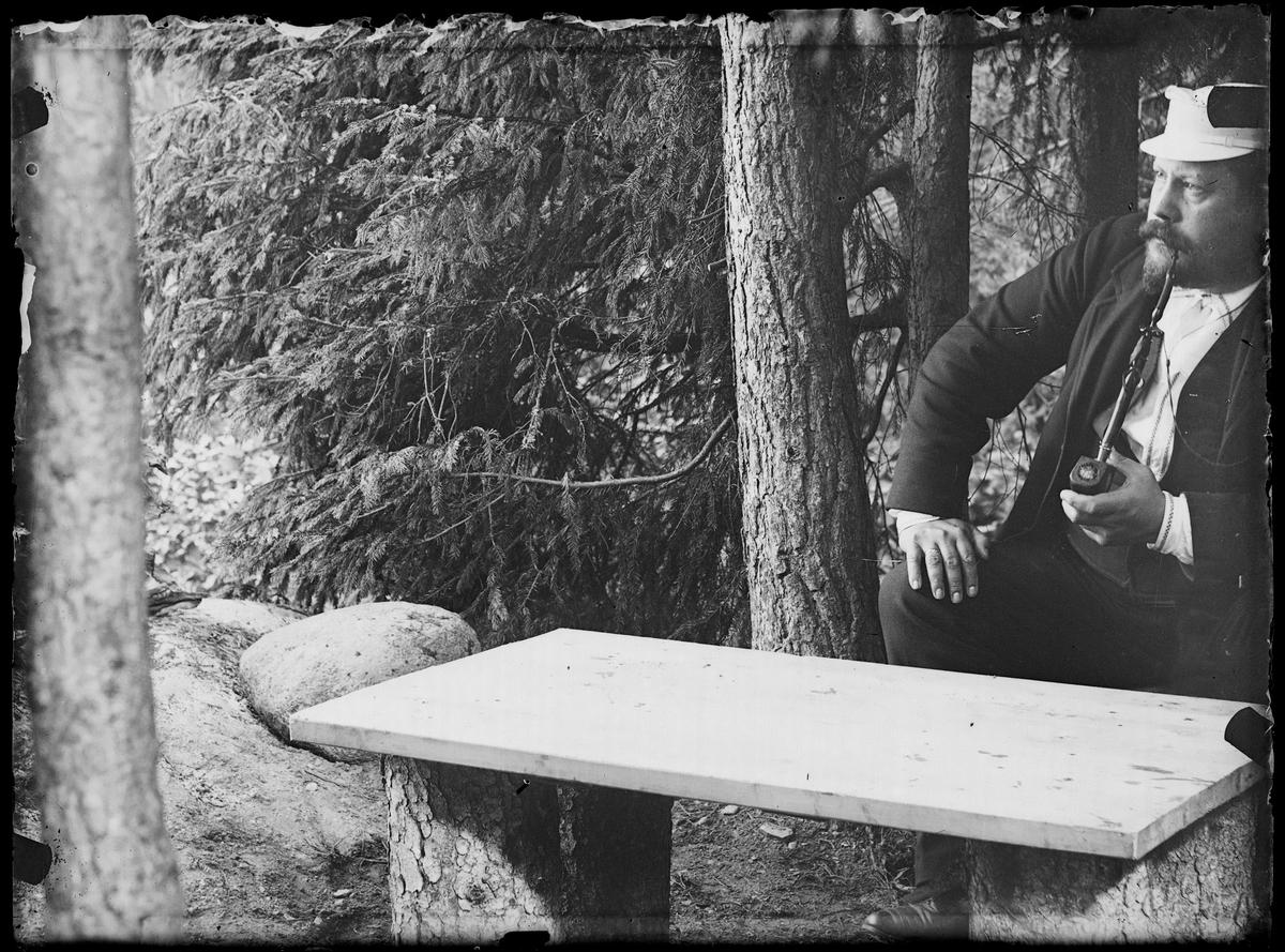 F.Grann-Meyer sittende med pipe ute under grantreet.