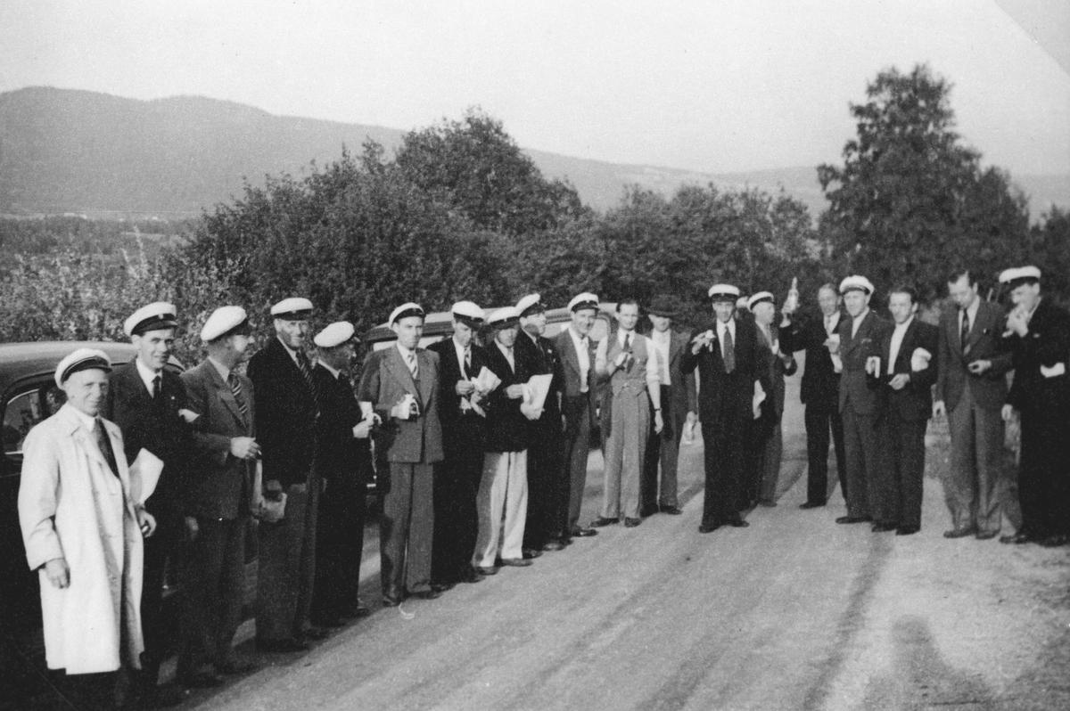 19 menn, stående på rad, de fleste med hvite uniformsluer. Bratland-kvartetten på tur i Valdres.
