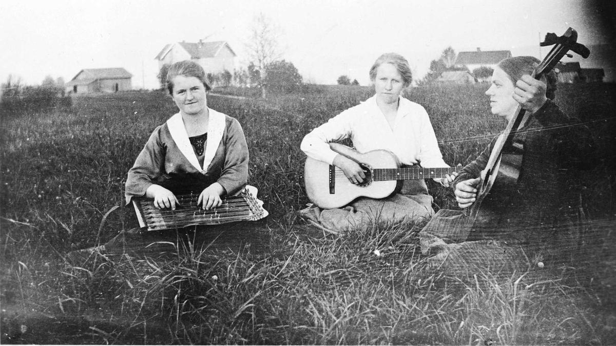 Tre damer med musikkinstrumenter ved Nordby skole.