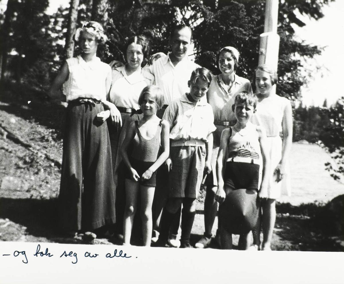 Åtte personer samlet foran en flaggstang. Fire barn og fire voksne ca. 1930
