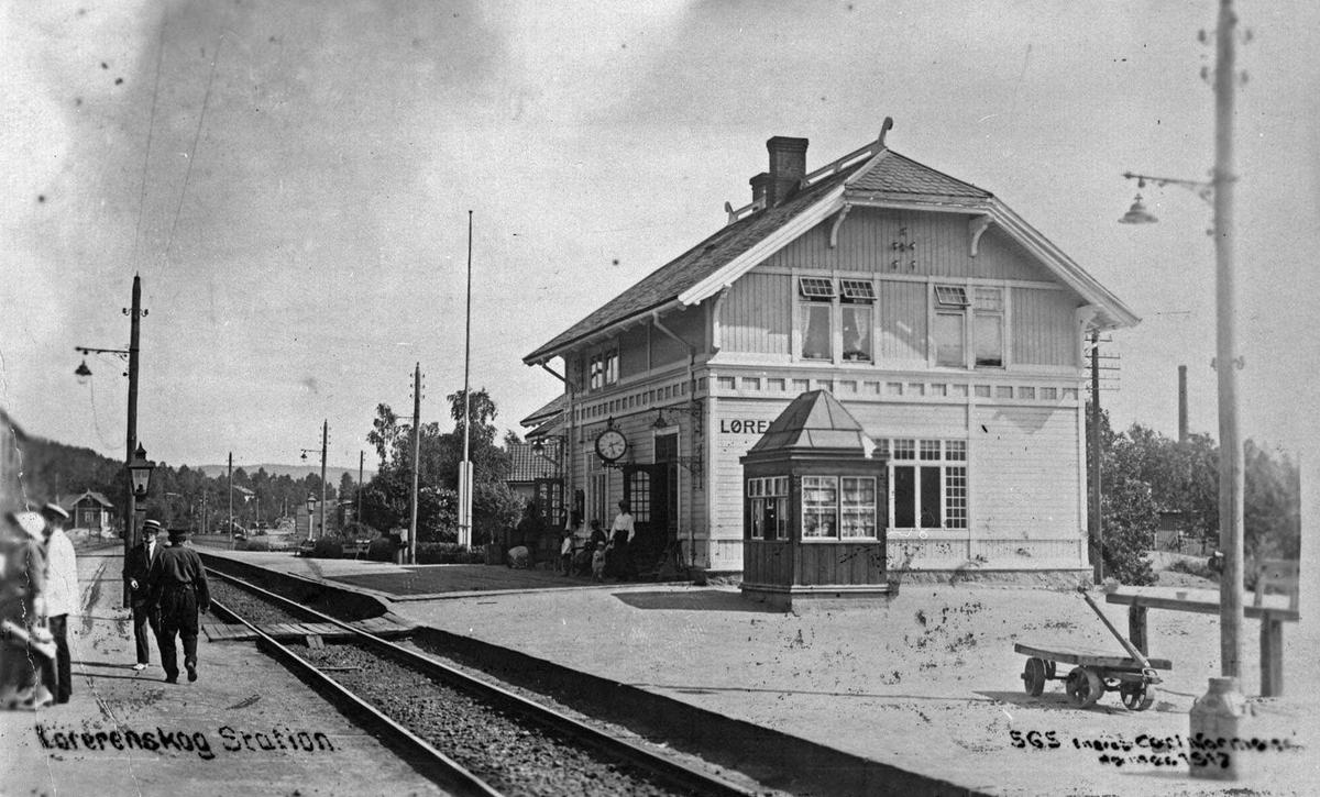 Lørenskog stasjon. Narvesenkiosken står foran stasjonsbygning. Stasjonsbygningen er levert fra Strømmen Trævarefabrik