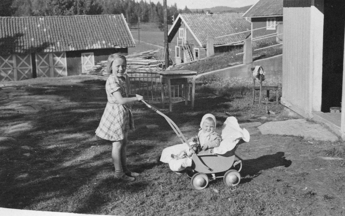Barn på tunet på Feiring gård. Pike passer baby i sportsvogn