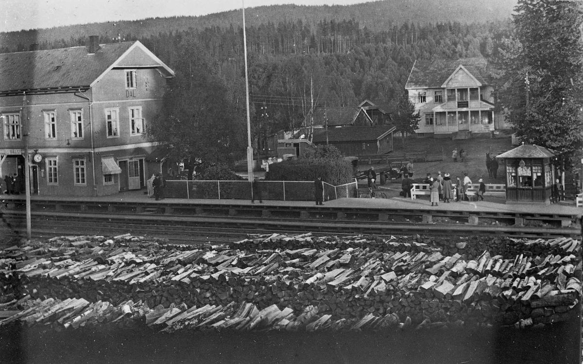 """Dal stasjon, hotell, kiosk og mellomkrigsmodell biler. Mellom 1917 og 1931. Huset i bakgrunnen med verandaen er """"Dalshaugen""""."""