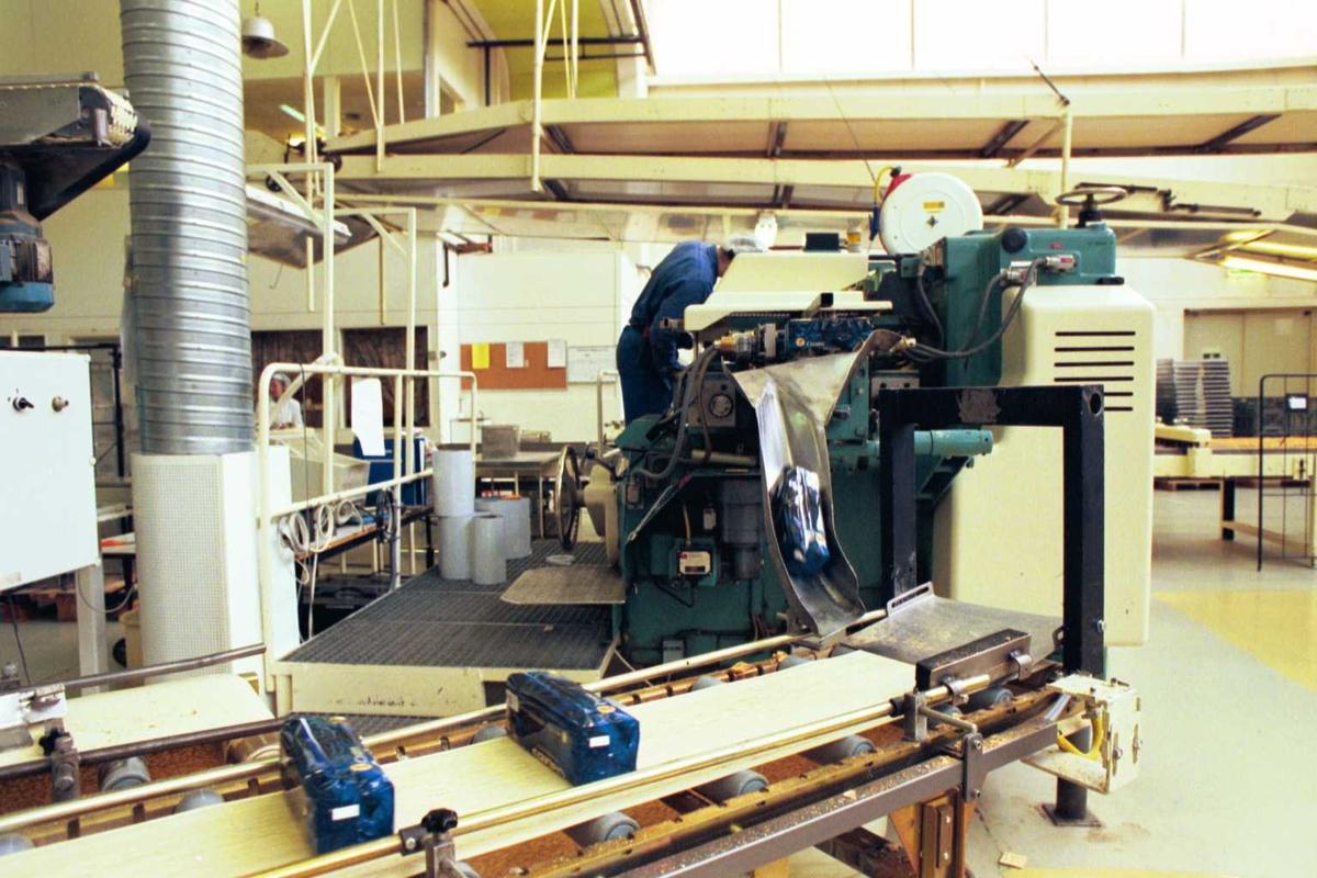 Cream Cracker, pakkemaskin, arbeider, kvinne, mann, fabrikkmiljø, arbeidsmiljø, arbeidstøy. Pakkemaskinen justeres av mannen i blått arbeidstøy.
