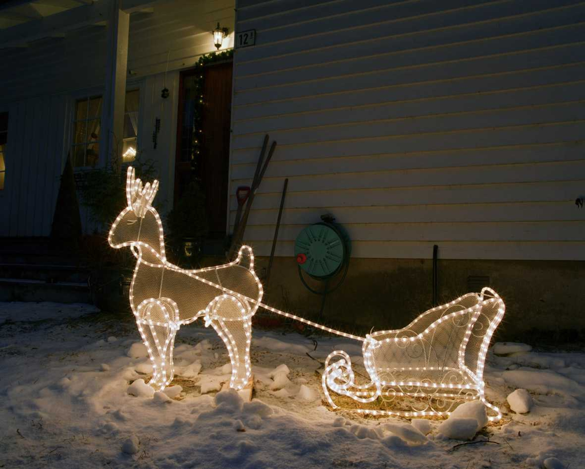 Julebelysning  Hvit lysende rensdyr med kane foran enebolig