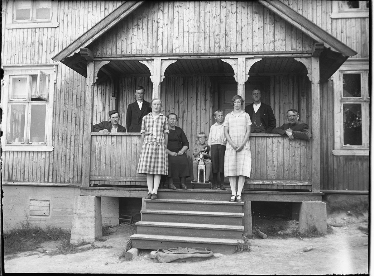 Ukjent gruppe, familie på trapp på ukjent sted. Jente med dokke på en gyngehest.
