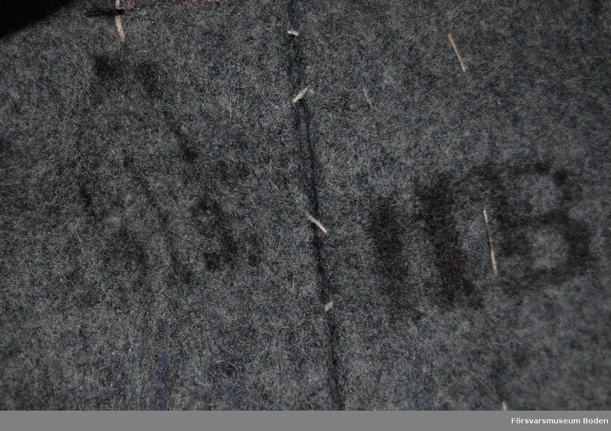 Kappa av kommisskläde utan regements- och gradbeteckningar. Dubbelknäppt med 5 släta bronsfärgade knappar i dubbla rader. Axelklaffarna har knappar modell större. Skörtet knäppt med tre knappar, och en hyska finns dessutom på varje sida för uppsättning. En knapp på vardera sidan för ryggslejfen som är av fast typ, fastsydd på ryggvecket som går från kragen ner till skörtet. Kappan har blivit insydd i ryggen. Spetsiga ärmuppslag utan blå passpoal, fästa med knapp.