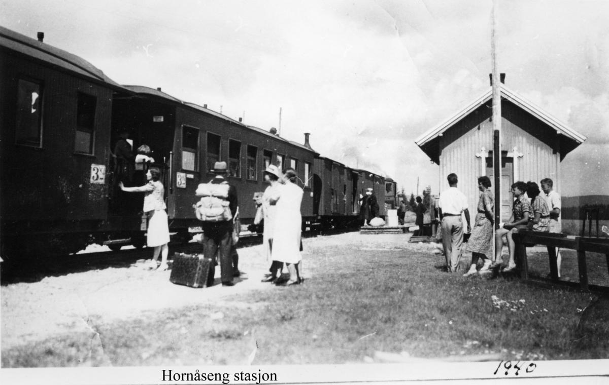 Hornåseng stasjon med tog retning Sørumsand og mange fremmøtte på stasjonen.