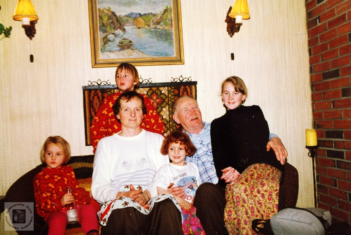 John og Margit Seland med barnebarn i farmors stove. Grindheim Audnedal.