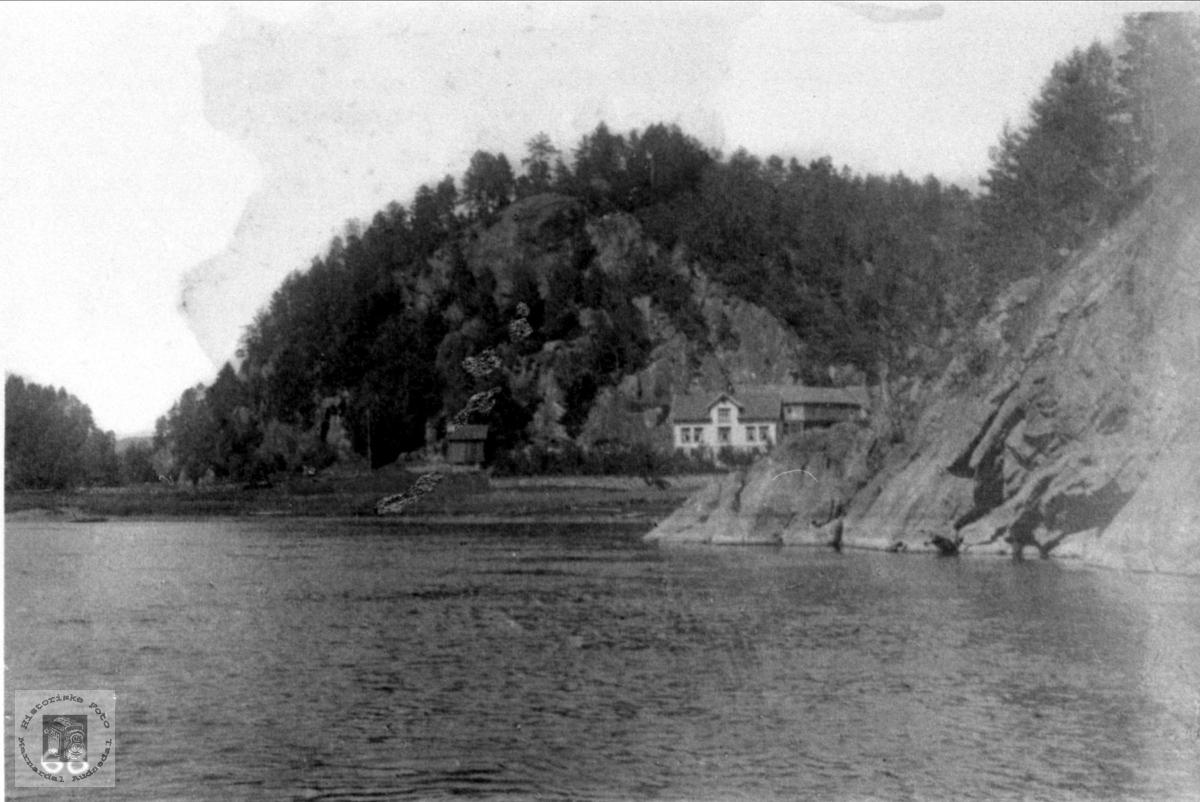 Fuglestveit (Olsgård) i Øyslebø med Mandalselva i forgrunnen.