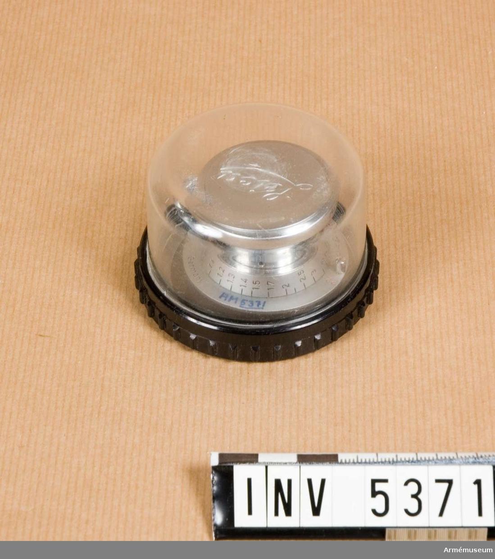 M 2708-130. Objektiv, l:40 mm, d:47 mm, hopskjutet 33 mm.       Matt vitmetall med svart skala för avstånd och röd för   skärpedjup och markering för infrarött (R). Tillv.nr 1296664. Gott skick. Objektivlock av matt vitmetall, röd sammet.Objektivet har brännvidden 50 mm och bländartalen 3,5 - 22.   Dessa regleras med en spak som kan bringas att rotera kring objektivets frontlins. Spaken sitter på en ring, på ringen finns  tillverkningsnumret. Objektivets tub låses innan fotografering  i utdraget läge medelst en vridning. I hopskjutet skick blir   kameran mycket platt, då objektivets större del finns i kamerans  inre. Objektivet låses vid oändligt för att underlätta dess   vridning då objektivet lossas från kameran. En knapp lossar   låset och objektivet kan fokuseras ner till 1 m. Optiken är   T-behandlad, d v s glaset är antireflexbahandlat; metoden är   uppfunnen av Zeiss. Emballage: plastburk i två delar, svart och glasklar. Exentriskt fäste för för objektiv kortare än 5 cm. Märkt 5043.1982-08-25