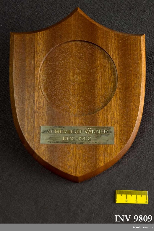 Samhörande nr är 9809-9810. Minnestavla Östergötlands flyghistoriska sällskap 1932-1982. En sköld i trä med urtag för den tillhörande medaljen. Under detta en silverplatta med texten: ARMÉMUSEI VÄNNER 1932-82.