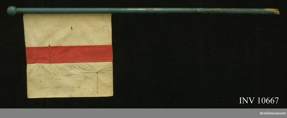 Grupp B.  Kompaniflaggan är utformad i enlighet med de år 1830 fastställda mössmärkena för infanterikompanierna. Duk av enkel vit bomullslärft med infällt dubbel röd lärft på  höjden mitt på duken. Blåmålad stång av furu med rund kula som spets.