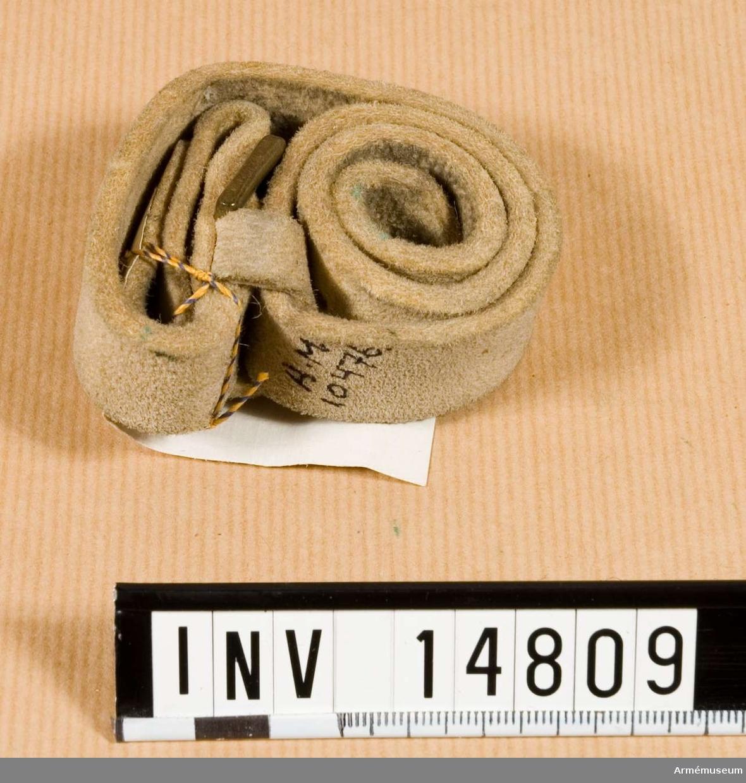 """Grupp C II. Av älgläder, 2 cm bred. Med spännen av mässing. Stämplad: """"1875"""" och """"WD."""" med uppåtriktad pil över """"W""""."""