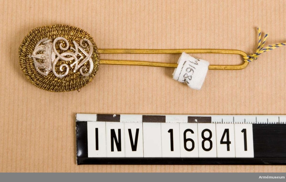 Pompong m/1865 med Konung G V:s namnchiffer. Pompongen är täckt med guldsnodd på framsidan och bär konungens monogram i silver. Baksidan har hål för hållaren av mässing och vid stor parad även för plymen. Till mössan m/1865-1899.