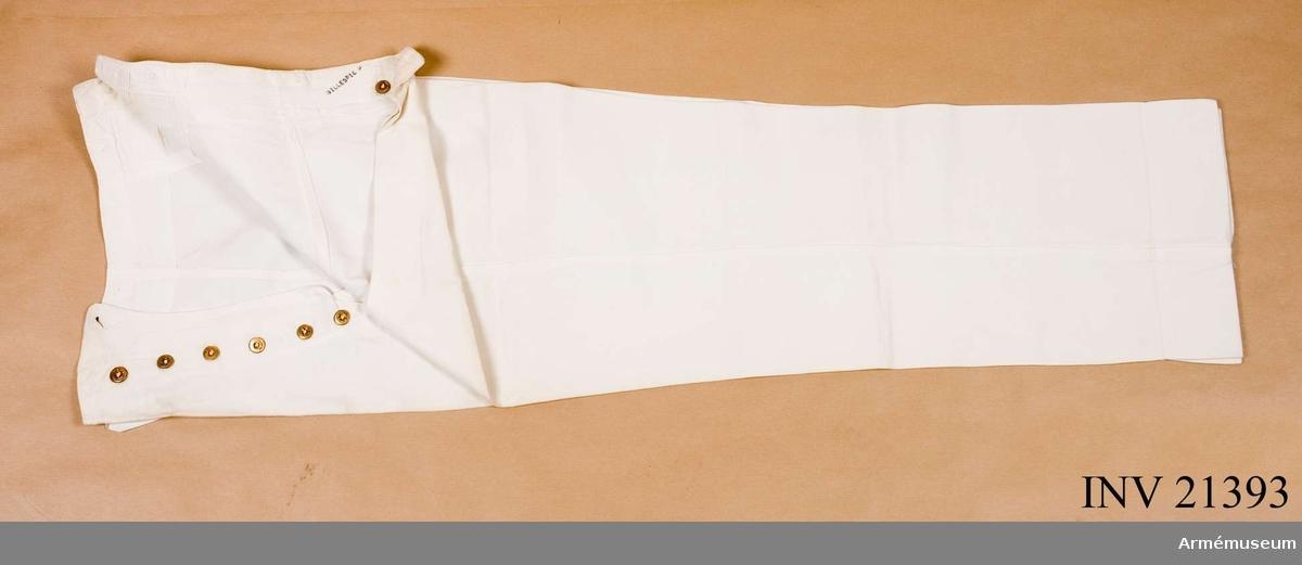 """Grupp C I. Av vitt linne. Endast en ficka, en liten vid midjan. Sprund med 6 knappar av gul metall med ingraverade bokstäver """"U.S.M.A."""" och två kvistar i kors: 1 knapp - d:17 mm, och 5 knappar med d:13 mm. För hängslen finns 6 st likadana knappar, d:17 mm. På baksidan en spänntamp av linne med spännen av gulmetall. På byxornas inre sida finns påskrift: """"Gillespie R."""" och fastsydd etikett av vitt tyg med påskriften: """"N 2354 Date 1-19-1939"""", """"Cadet Store"""" West Point. """"Name ....."""", """"Maker: S.K."""" På fållarna finns upplägg, b:70 mm. LITT  Armeen Album III U.S.A. Die Armée der Vereinigten Staaten von Amerika. Von de Witt Clinton Falls Verlag von Moritz Ruhl, Leipzig. Sida 15. """"Das militärische Erziehungs- und Unter- richtswesen"""". Kort beskrivning om Militär Akademi i West Point. Bilaga: Bild i färger. Sida 5. Olika kadettuniformer. """"Kadett Parade uniform"""". På kadetten - vita, långa byxor.Handbuch der Uniformkunde, Prof. Richard Knötel, Hamburg 1937. Sida 398. År 1813 alla Jägerregementen i amerikanska armén har uniform av grått kläde. I denna gråa uniform Jäger regementet N 4 visat stor tapperhet vid slaget Chippowa Plains och Niagara Militair Akademie West Point erhöll snart denna uniform från Jäger regementet N 4 till Eran. Kadetterna tills idag har samma tradionsuniformer från detta regemente.Enl Granberg."""