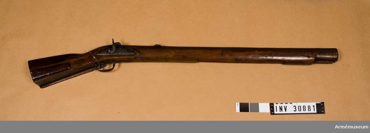 """Grupp E XII.  Ursprungligen en sälstudsare med flintlås, 1700-tal.  Pipan är åttkantig och brungjord. Något framför bakänden har den på översidan en otydlig smedsstämpel och söderhamna stämpel, ett par korslagda gevär över en båt. Framför dessa stämplar är EKM inristat i pipan. Svansskruvsstjärten är jämnbred. Pipan fasthålles av en uppifrån isatt korsskruv och två häften. Knallhattstappen sitter i en i pipan inskruvad """"snäcka"""". Loppet har 8 räfflor. Ett smalt, 2 cm långt silverkorn sitter 7 cm bakom pipmynningen. Siktet är placerat 15,5 cm framför pipans bakände. Det är av den vanliga rännliknande, svenska typen. Väggarna är 3,5 cm långa och, sedda från sidan, bågformigt avrundade. Siktbalken är av bly.  Låset, som ej är det ursprungliga, vilket tydligen varit ett snapplås, insattes vid ändringen från flint till knallhattsantändning, är taget från ett av det engelska infanterigevär m/1762, vilka 1808 inköptes och 1812 som subsidier i stora mängder kommer från England till Sverige. Låset har ändrats till slaglås. Blecket är på utsidan märkt med Georg III:s namnchiffer G R och en bakåtriktad, krönt pil samt på bakspetsen med """"TOWER"""". Det fasthålles blott av en skruv. Vapnet har helstock av björk. Kolven påminner om teschitzbössornas, vilken kolvform på 1600-talets senare hälft och på 1700-talets början ofta användes på svenska lodbössor av bättre kvalitet.  Kindstödet är blott neddraget omkring 1 cm nedanför kolvens underkant. Framtill avslutas kindstödet av ett snidat ornament. På kolvens högra sida finns en med skjutlock försedd kolvlåda. Framstocken har kräva, som är gjord i ett stycke med stocken. Beslagen består av bakplåt, ett litet ovalt sidbleck samt avtryckarebleck och varbygel. Alla beslag är av gråhärdat järn, men de bägge sistnämnda syns tagna från ett äldre jaktgevär.   Laddstocken av trä och har i smaländen en 24,5 cm lång skoning av mässing, i vars ände ett gängat hål för kratsen anbringats.I kolvlådan ligger en krats av järn. Bössan är bättre arbetad """
