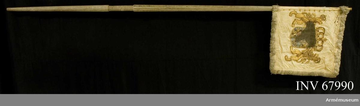Duk: Enkel, tillverkad av vit sidendamast, sammansydd av två våder (horisontell skarv). Duken fäst vid stången med tre rader tennlikor på ett vitt sidenband.  Dekor: Målad lika på båda sidor: Svenska riksvapnet under pfalziska huset krönt med stor, sluten krona med pärlor i silver, såsom sköldhållare gyllene, med slutna kronor krönta, dubbelsvansade lejon med röda tungor.  Frans: Dubbel vit silkesfrans.  Stång av trä, kanellerad, gråvitmålad.