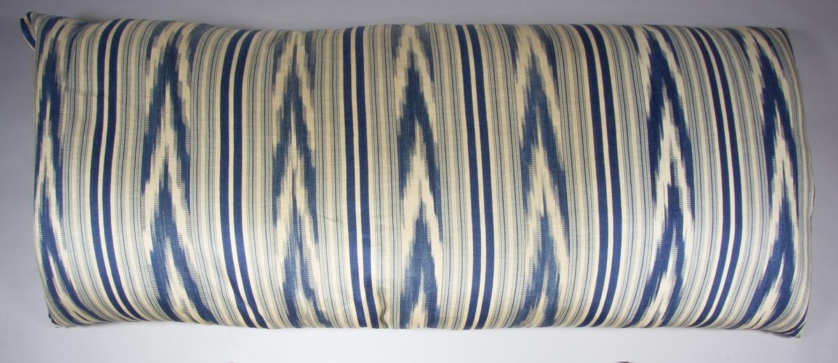"""Bolster, tillverkat med framsida av handvävt tyg, lin, satinvävt, med vit linvarp och inslag i vitt, ljusblått och mörkblått lingarn, trådränder med klarblått. Bolstret är mönstrat både med """"vanliga"""" ränder och med flamgarnsränder. Baksida av vitt kypertvävt linnetyg. Bolstret är sytt så att framsidan råder över baksidan. Fyllning: fjäder."""