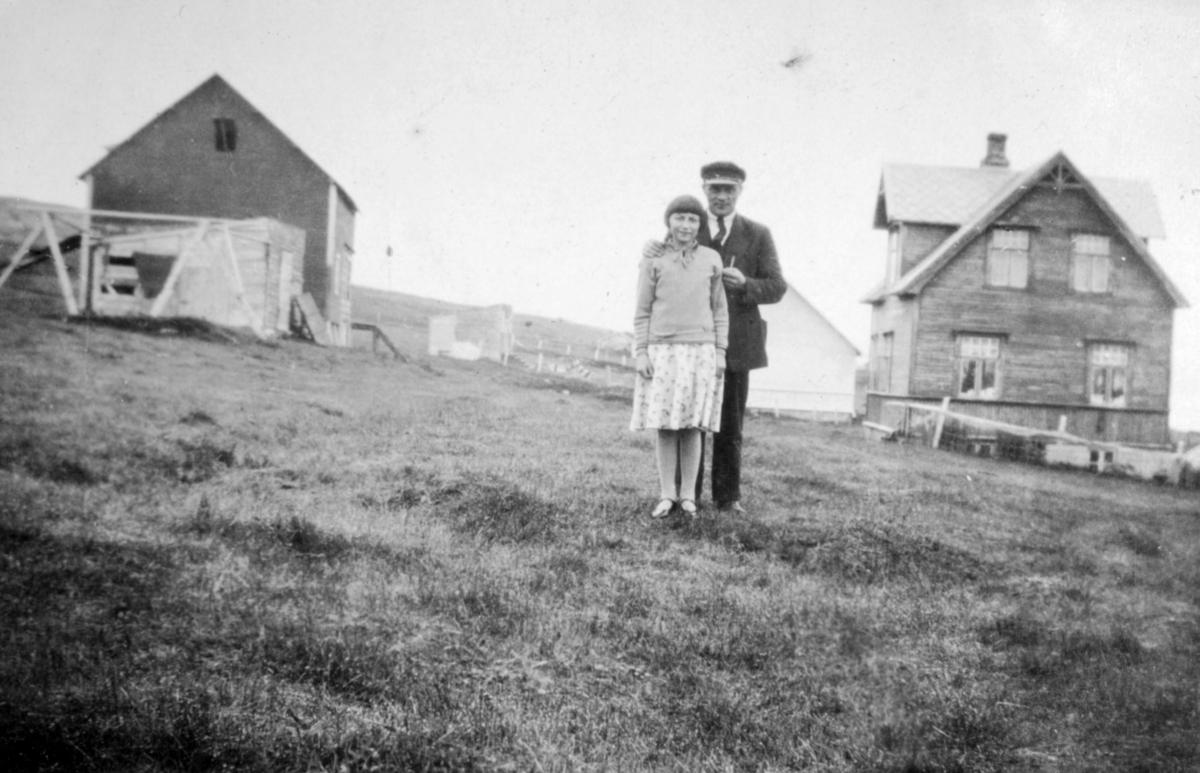 En mann og en jente, muligens far og datter, poserer for fotografen på et jorde. Flere bygninger ses i bakgrunnen. Sted og personer er ukjent, men bildet kan være tatt i Kvalsund kommune.