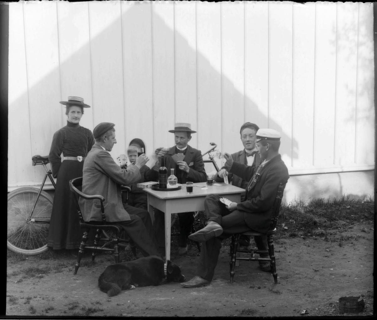 Fire menn spiller kort ute i solveggen