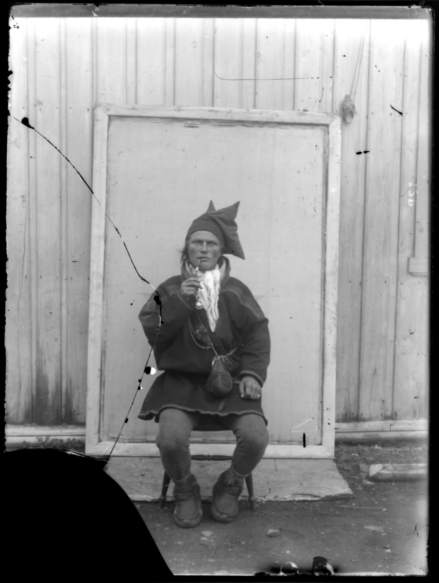 Samisk mann i kofte fotografert foran en lys bygning