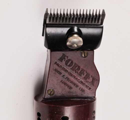 Klippemaskin med ledning. Sylinderformet bakelitthåndtak i burgunder farge med opphengsring, av/på bryter og kobbersplint med gummibeskyttelse bak.  Opphengsringen er festet til ledningsuttaket.  Klippehodet er festet til maskinen med en skrue med riller for grep, og sitter på en rektangulær avfasning av håndtaket.