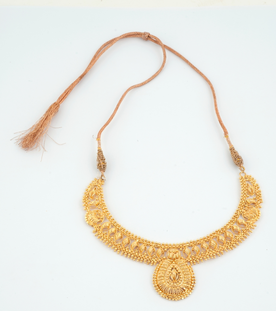 Gullfargede smykker til brudedrakt. Består av 9 armringer, et par øreheng, 2 halssmykker og 2 anheng = ukjent bruk