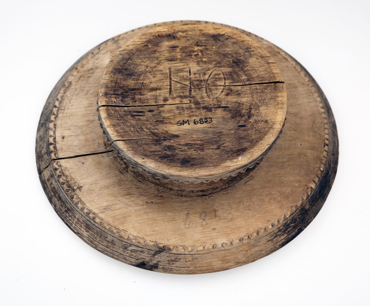 Rundt fat på stett med en liten fordjupning. Rundt kanten på fatet og nederst på stettet er det skåret ut et mønster (en geometrisk bord)