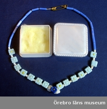 1)  Vit-ljusblå-blå barnhalsband av porslinspärla med säkerhetsnål som lås i ask.2)  Vit bakelit ask (4,3x4,3 cm)PS: 330   Acc: 2005/24