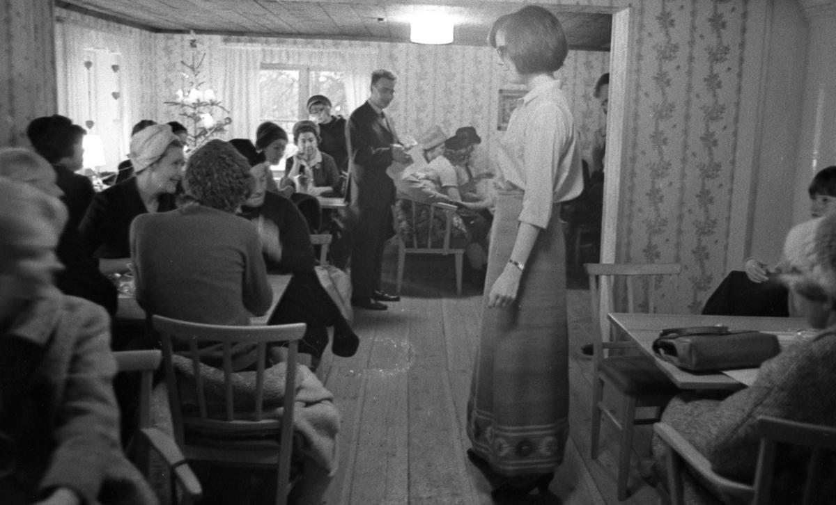 Lungkliniken, Nappivalen, Grekiskt handarbete 11 december 1967En modevisning inne i ett rum i ett hus. En fotomodell klädd i en ljus blus med trekvartslång ärm, en mönstrad kjol av grekiskt handarbete och svarta, lågklackade pumps står mitt på golvet. Publik sitter på stolar vid bord och betraktar henne.