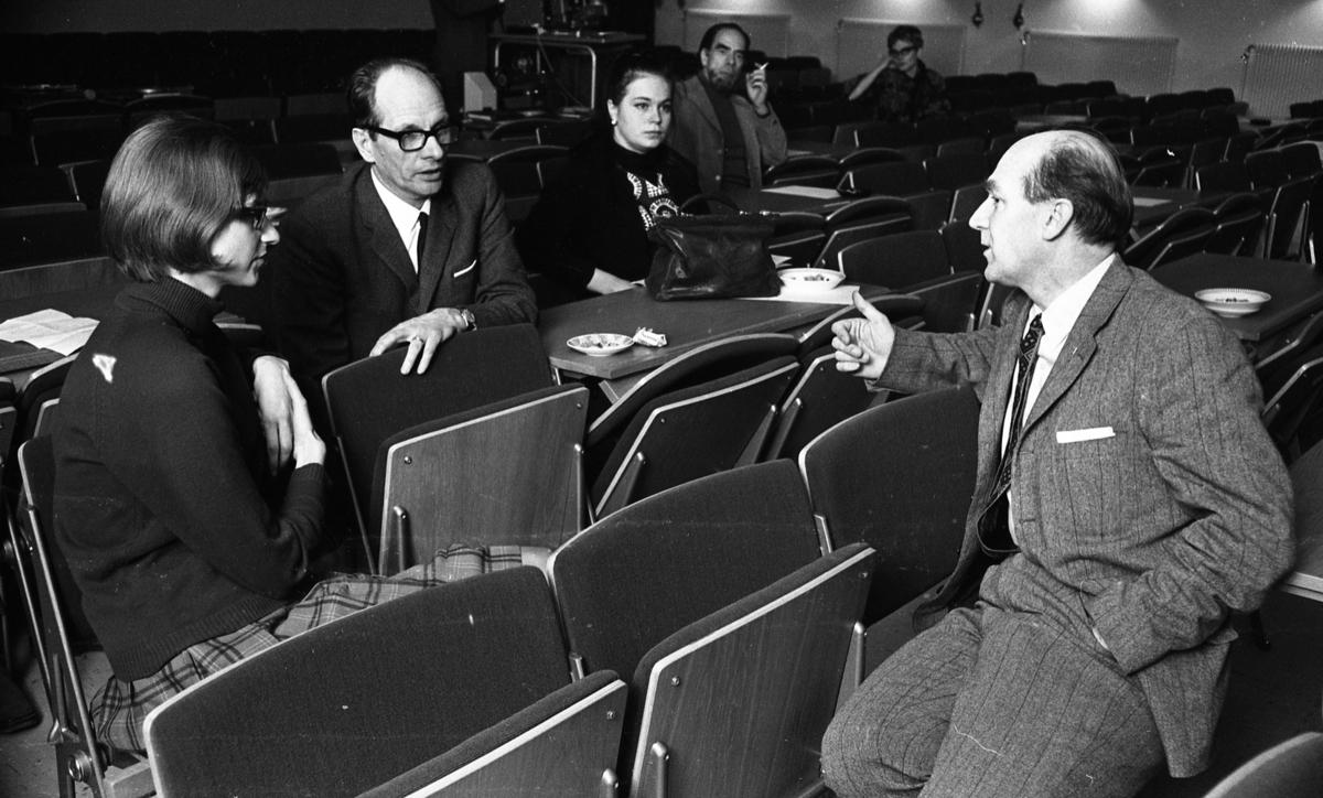 Lärare lärde film, Hantverksbutik, Hans Alsér, Ingenjörer på kurs 18 november 1967Sex lärare sitter utspridda på olika stolar i en aula. De lär sig om ämnet film. Det är tre kvinnor och tre män. Kvinnan närmast är klädd i långärmad, svart tröja och ljus rutig kjol. De två herrarna närmast kameran är klädda i kostymer, vita skjortor och slipsar.