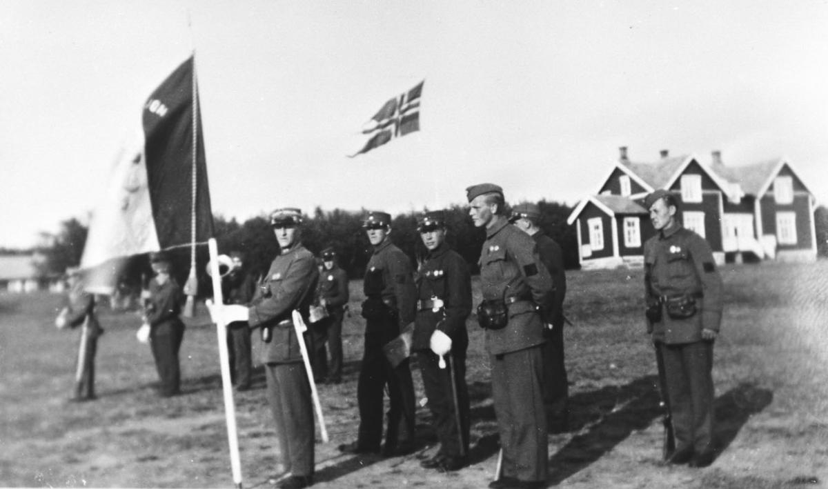 Vi antar at bildene er tatt i forbindelse med gjenopprettelse av Varanger batlajon 01.07.1934. Offiser holder flagg, bak står to offiserer og to soldater. Helt til venstre skimtes en del av musikkorps. Bildet er tatt på eksersersplassen på Nybergmoen 1934. I bakgrunnen sees soldaterhjemmet. Flagget som offiseren holder er av ukjent art. Mulig fane for bataljonen ?  Motivet nesten identisk med 99011-003.