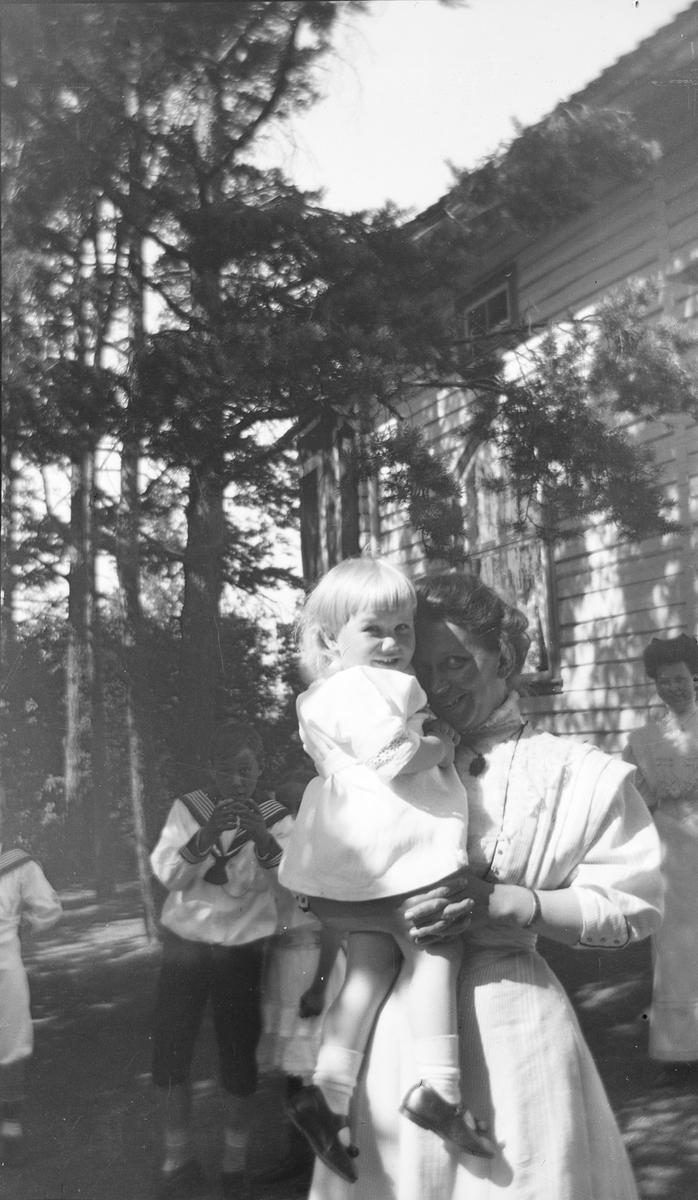 En kvinne har Iacob Ihlen Mathiesen på armen, som hun holder tett inntil seg. I bakgrunnen sees også tre andre, litt større, barn og en kvinne. Alle er de foran et hus hvor furu og bjørk vokser nært huset.