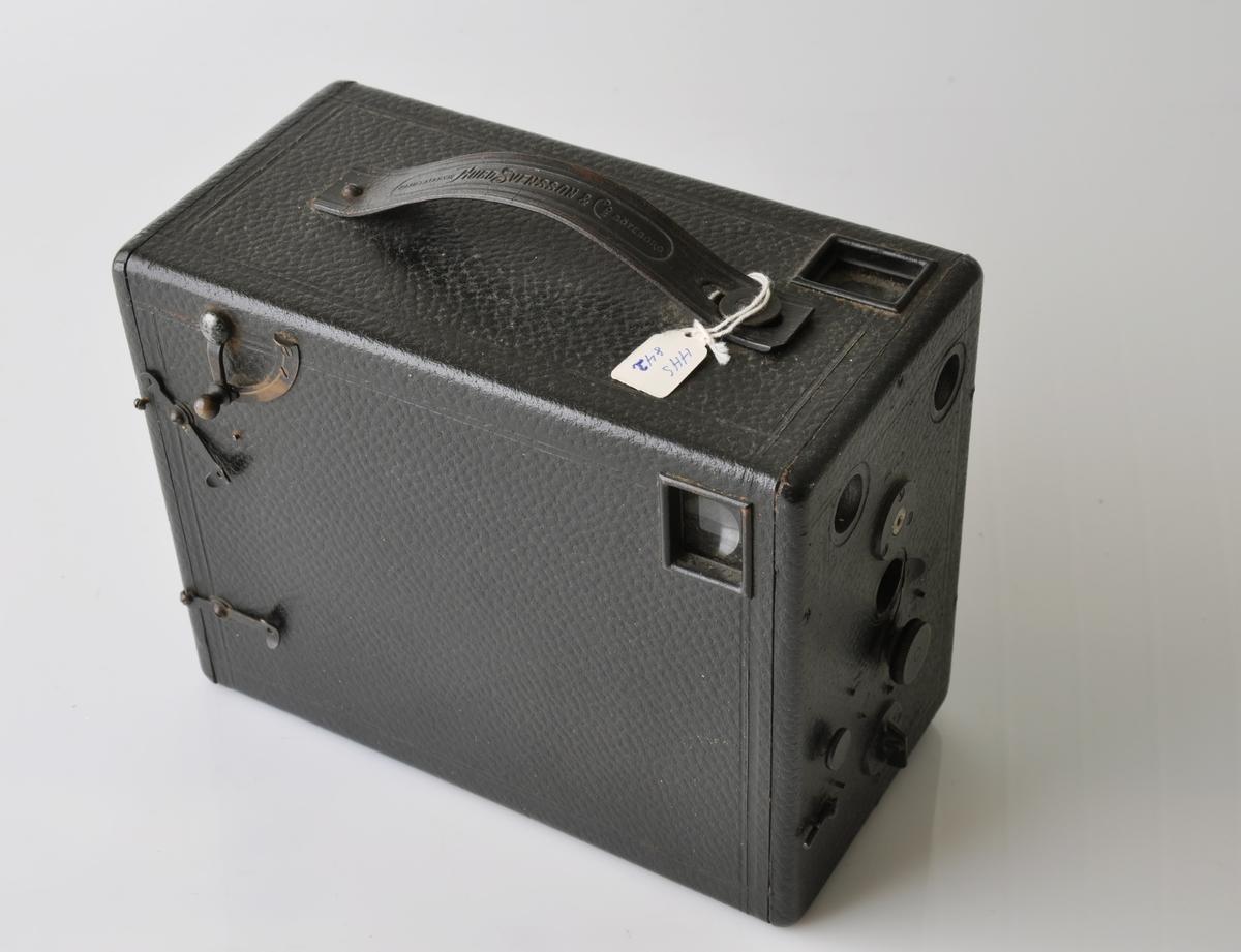 """Form: Trekasse trukket med """"sjirting"""". På toppflaten, håndtak av skinn. Bak, merket med metallskilt. Platefilm- kamera. Fronten har: Avstandsinnstilling, blenderinnst., tidsinnst., og O-M-T innst. og nr. 13833"""