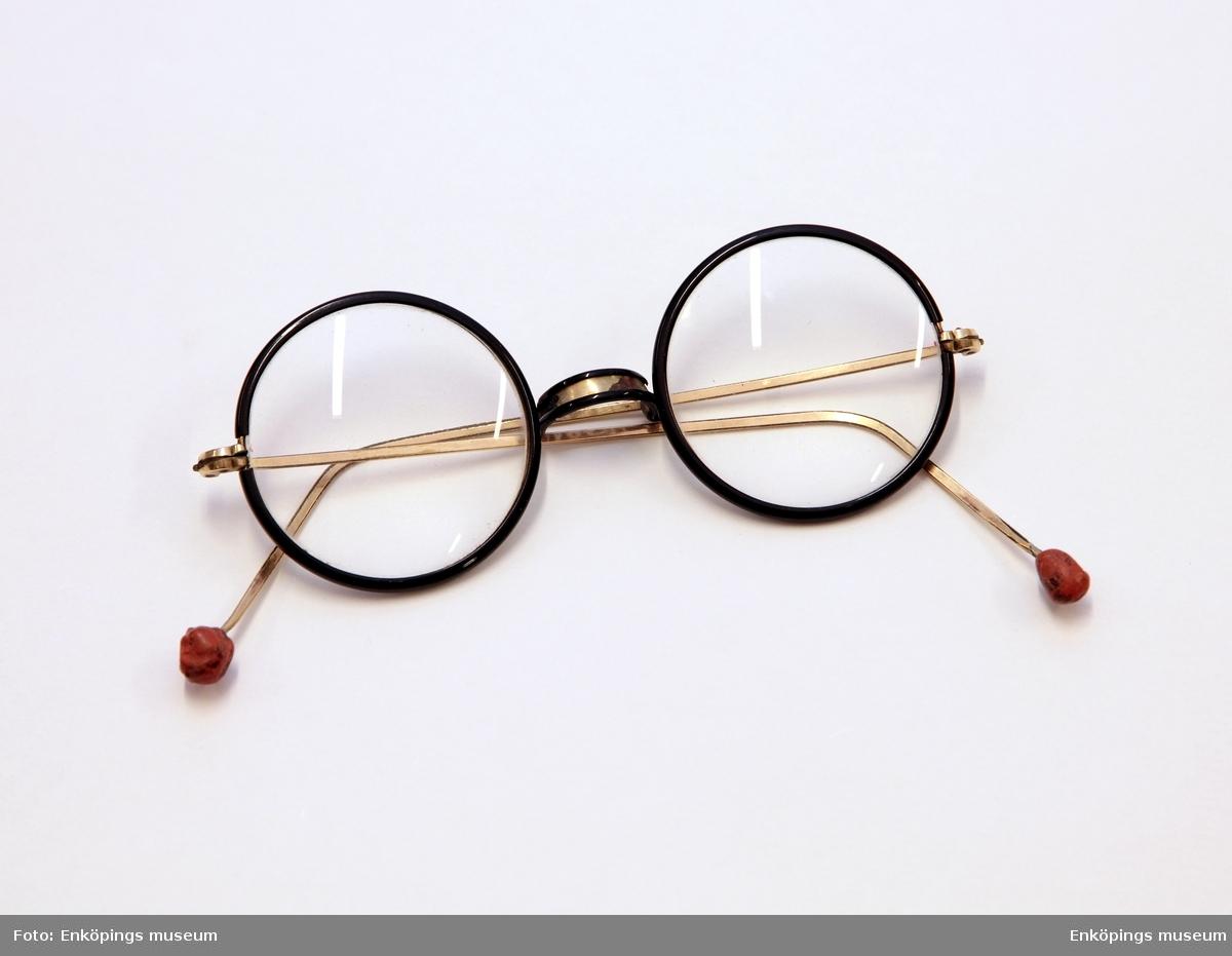 Runda glasögon, metallstomme som klätts med svart backelit (?) runt glasen. Näsbygel av metall- klädd på baksidan av backelit ( e dyl). Skalmarnas ändar försedda med små kulor av röd sigilllack.