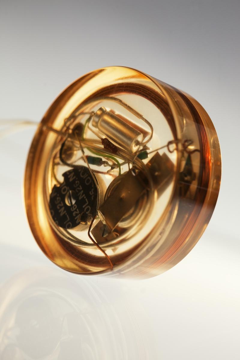 Pacemaker för implantat, med ett fåtal ingående komponenter. Ingjutet i kloss av epoximaterial med två elektroder för stimulans av hjärtverksamheten.