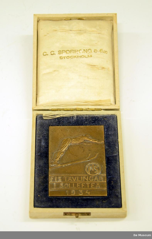"""Deltakermedalje, """"minnemynt"""". Fra Sollefteå, Sverige. FIS-hopprenn i 1934. Medaljen er laget av bronse, og ligger i etui. Innskrift: FIS TÄVLINGAR I SOLLEFTEÅ 1934."""