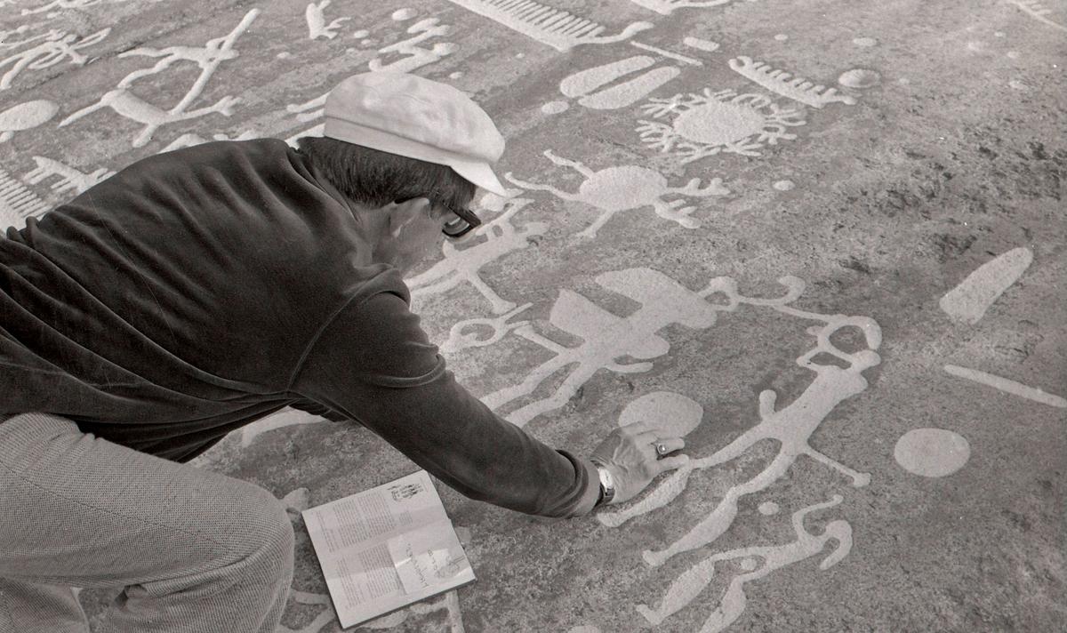 """En man som studerar hällristningar. Hällristningsområdet i Tanum är ett område i Tanums kommun i Bohuslän där man funnit flera berghällar med stora mängder hällristningar från bronsåldern. Runt den största av dem, Vitlyckehällen, är Vitlycke museum uppbyggt. Hällen har närmare 300 inhuggna figurer och ca 170 skålgropar. Den kanske mest berömda scenen bland alla Tanums hällristningar, """"Brudparet"""", finns här. Bland de övriga närliggande hällarna märks Litsleby med en ca 2,3 meter lång spjutbeväpnad man, """"Spjutguden"""", och Aspeberget med en plöjningsscen, ett antal oxar och skepp. Hällen vid Fossum ligger en bit från de övriga. Den kännetecknas av en mer sammanhållen och konstnärlig komposition. Kanske är den gjord av en enda ristare.  Hällristningarna har i modern tid fyllts i med röd färg för att göra dem tydligare. Det är inte känt om de var målade från början.  (Hämtat från Wikipedia)"""