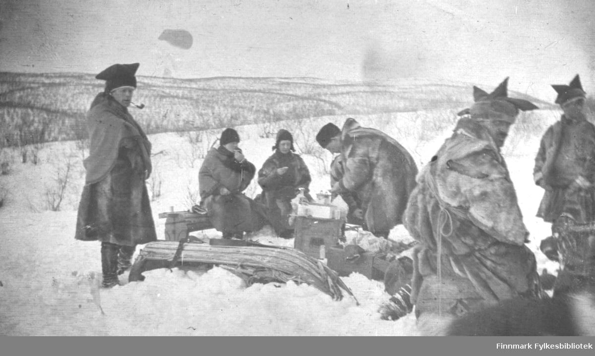 Aimjok,1916. Samer i pesk med karakteristisk samisk lue. En av mennene røyker pipe. Noen sitter med mat eller drikke i hendene.