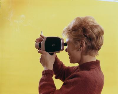 Reklamefoto fra Tiedemanns Tobaksfabrik. Kvinnelig modell med sigarett og filmkamera.