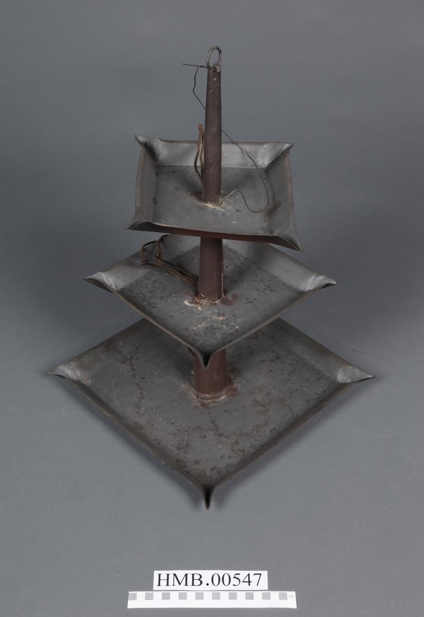 Kvadratiske skåler i tre størrelser, satt sammen i konisk form. I de fire hjørnene på hvert kvadrat er det plass til veker. De to nederste kvadratene står i samme vinkel over hverandre, hjørne over hjørne. Det øverste kvadratet står med hjørne over rettsiden til de to andre kvadratene. På toppen av lampen er det et rundt feste, til å henge den opp. I festet er en ståltråd. Det er satt inn ledninger i lampen, slik at den kunne brukes med elektrisitet.