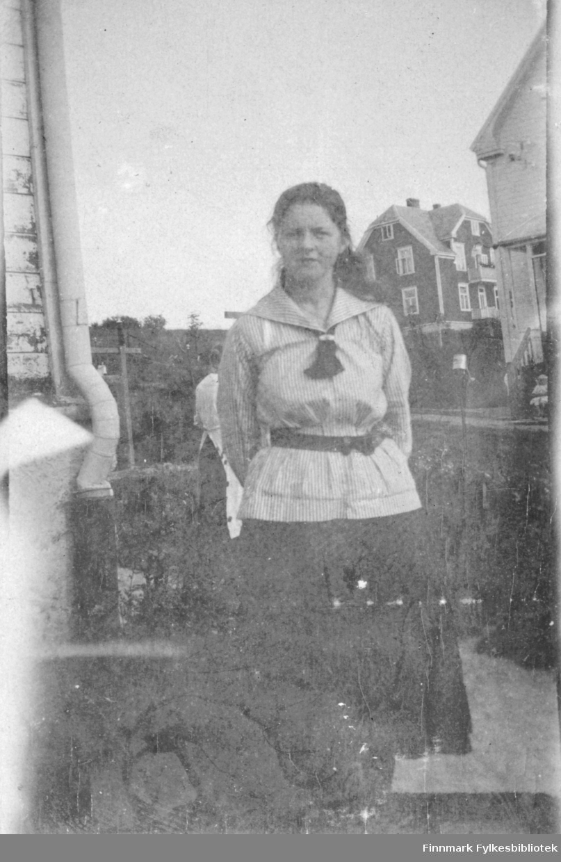 Kvinne stående mellom hus, i matrosbluse.
