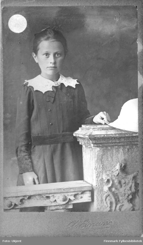 Påskrift på bildet: 'Tante Borghild Mathisen, 9 år'. Hun har på seg en kjole med et tøybelte og knapper. Hun har også en dekorativ krage med en brosje på. Hun ser ut til å holde på en hatt og lener hånden på en søyle.