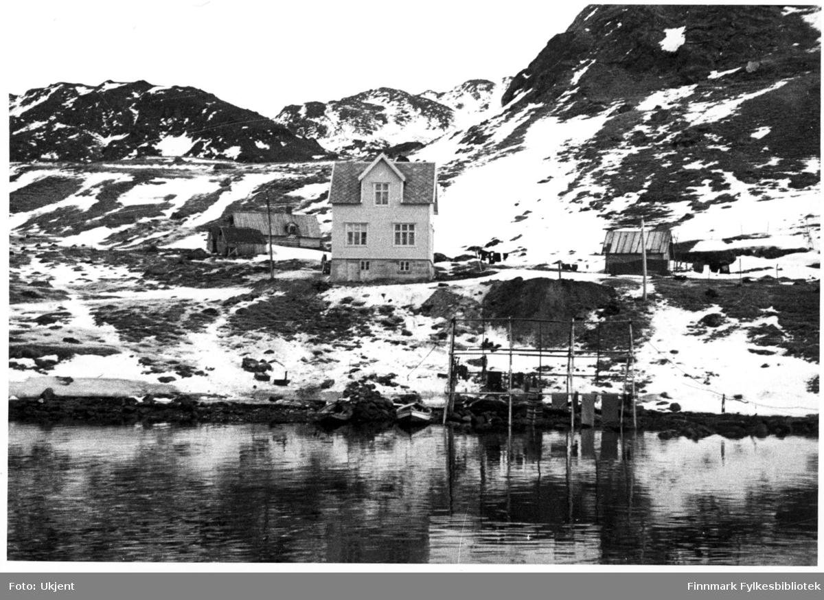 Bildet tatt i Sør-Tverrfjord og viser en oversikt over småbruk, båter og fiskehjell. På husene kan man se tak, vindu og grunnmur. Hjellene er plassert i fjæra.